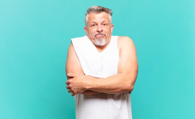 Старший спортсмен мужчина пожимает плечами, чувствуя смущение и неуверенность, сомневаясь, скрестив руки и озадаченный взгляд