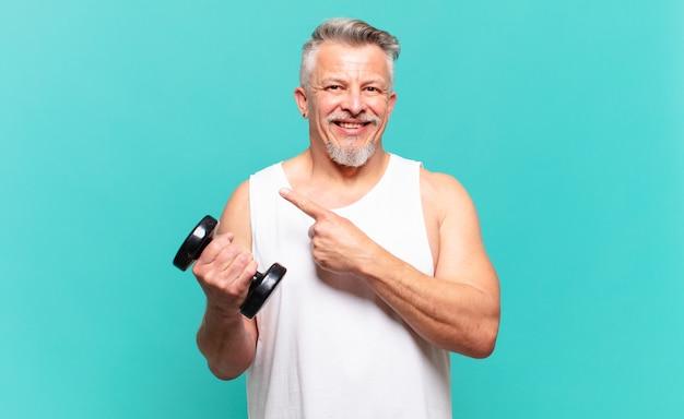 Старший спортсмен мужчина весело улыбается, чувствует себя счастливым и указывает в сторону и вверх, показывая объект в копировальном пространстве