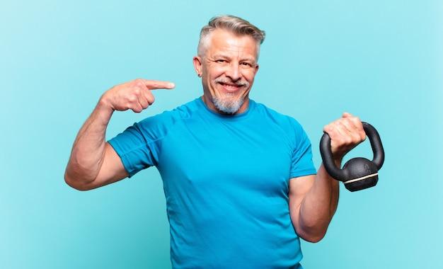 자신의 넓은 미소, 긍정적이고 편안하고 만족스러운 태도를 자신있게 가리키며 웃고 있는 시니어 운동선수