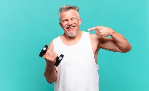 자신의 넓은 미소, 긍정적이고 편안하며 만족스러운 태도를 자신있게 가리키며 웃고 있는 시니어 운동선수