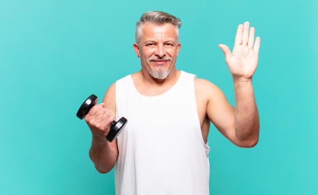 Старший спортсмен улыбается счастливо и весело, машет рукой, приветствует и приветствует вас или прощается