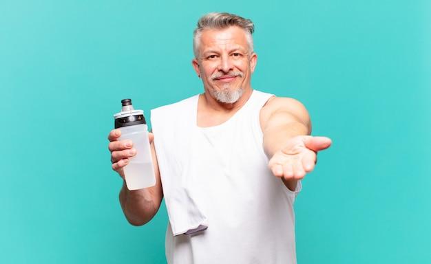 Старший спортсмен-мужчина счастливо улыбается, дружелюбно, уверенно, позитивно смотрит, предлагая и показывая объект или концепцию
