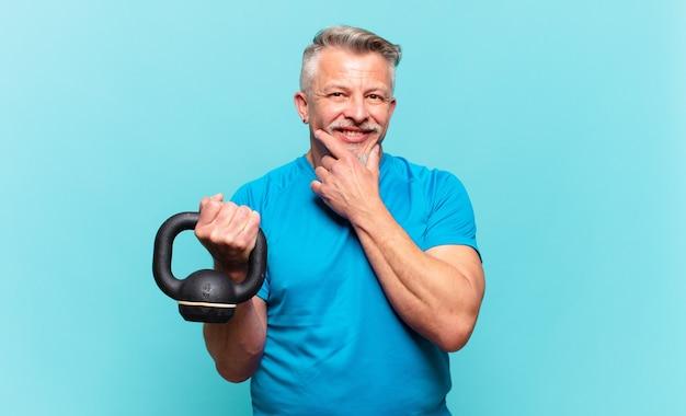 Старший спортсмен мужчина улыбается со счастливым, уверенным выражением лица, положив руку на подбородок, задается вопросом и смотрит в сторону