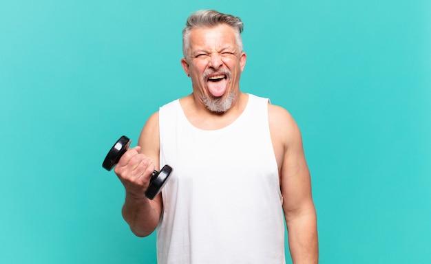 Старший спортсмен-мужчина с веселым, беззаботным, бунтарским отношением, шутит и высунул язык, весело