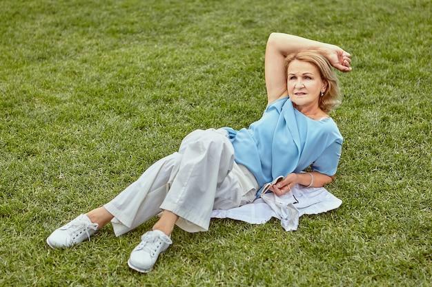 캐주얼 우아한 옷감에 약 60 세 수석 매력적인 백인 여자는 낮에 공공 공원에서 잔디에 누워있다.
