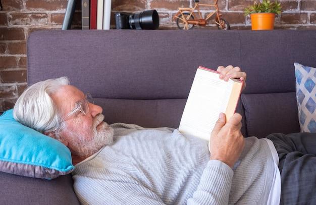 Старший привлекательный мужчина, лежа на диване, читая книгу старый пенсионер, отдыхающий дома кирпичная стена