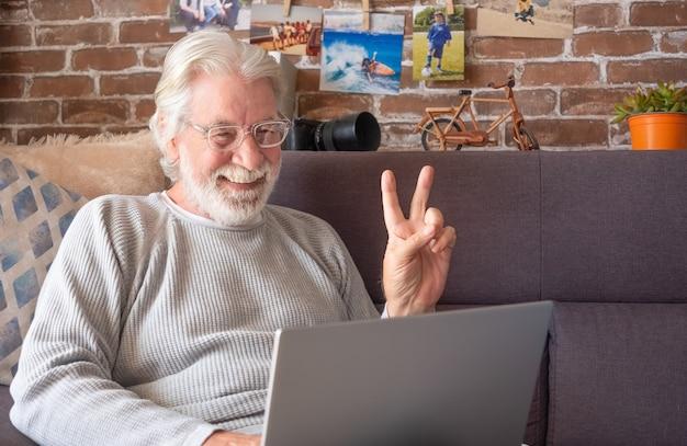Старший привлекательный мужчина с помощью ноутбука в видеозвонке. старый пенсионер проводит свое время, работая дома на ноутбуке с фотоаппаратом, украшениями, фотографиями. фон кирпичной стены