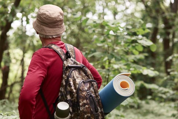Senior backpackers walking along road in forest, elderly traveller wears red casual sweater, cap, rucksack