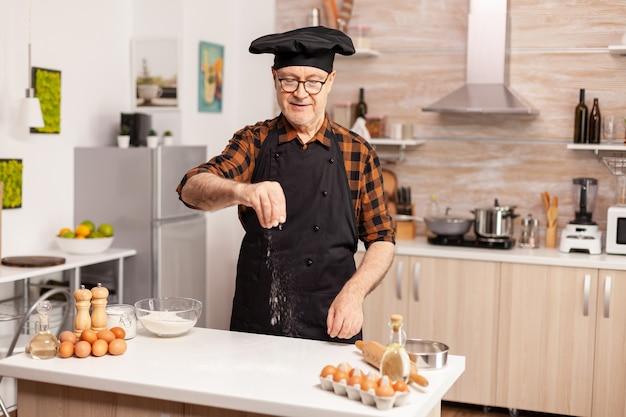 Fornaio senior che spolvera farina di frumento sul tavolo da cucina di casa per una ricetta gustosa