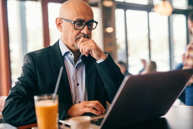 シニアのひげを生やした実業家のあごに手を握って、カフェテリアに座っている間仕事のためにラップトップを使用して。