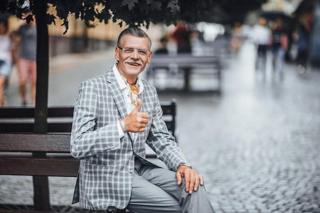 Старший бородатый бизнесмен, показывающий хорошее расположение на улице