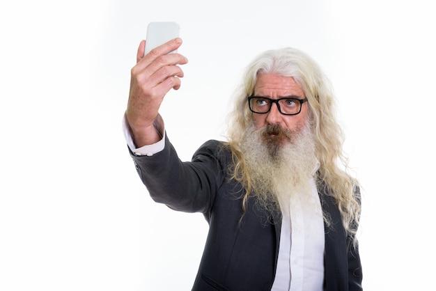 自撮り写真を撮るシニアひげを生やしたビジネスマン