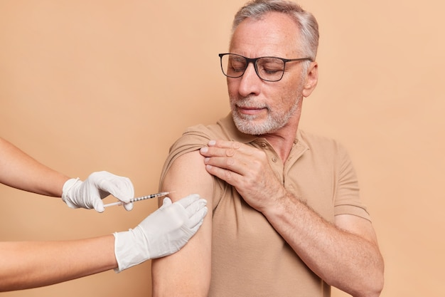 Senior bearded grey haired man gets vaccine in arm takes care about health during coronavirus pandemic wears spectacles and casual t shirt isolated over beige wall
