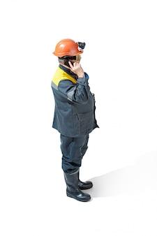 白のカメラに立っているシニアのひげを生やした男性鉱山労働者