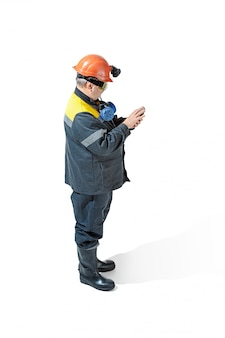 Senior bearded male miner standing at the camera on a white