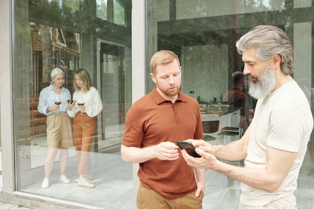 Senior bearded man asking adult son about smartphone app while they talking about technology in cottage house
