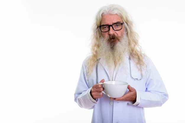 コーヒーカップを保持しているシニアひげを生やした男の医者