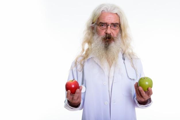Старший бородатый мужчина доктор держит красное яблоко и зеленое яблоко