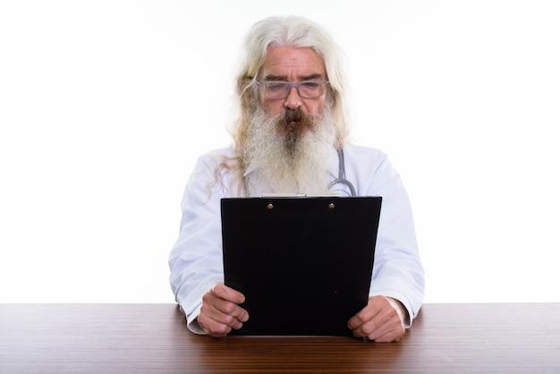 Старший бородатый мужчина врач в очках на деревянном столе