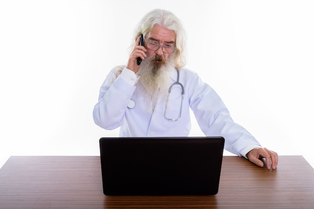 Senior bearded man doctor wearing eyeglasses while using laptop