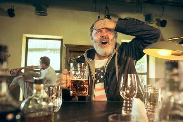 パブでアルコールを飲み、テレビでスポーツ番組を見ている年配のひげを生やした男。ビールを楽しんでいます。テーブルに座っているビールのマグカップを持つ男。サッカーやスポーツのファン。バックグラウンドでのファンの戦い