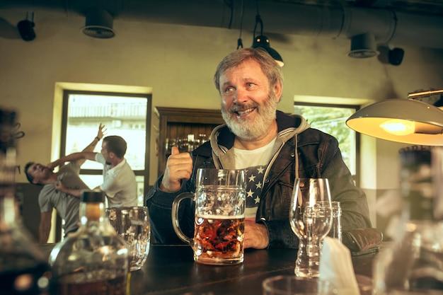 술집에서 술을 마시고 tv에서 스포츠 프로그램을 보는 수석 수염 남자. 맥주를 즐기고있다. 테이블에 앉아 맥주 머그잔을 가진 남자입니다. 축구 또는 스포츠 팬.