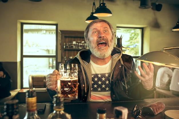 술집에서 술을 마시고 tv에서 스포츠 프로그램을 보는 수석 수염 남자. 내가 가장 좋아하는 팀과 맥주를 즐기고 있습니다. 테이블에 앉아 맥주 머그잔을 가진 남자입니다. 축구 또는 스포츠 팬. 인간의 감정 개념