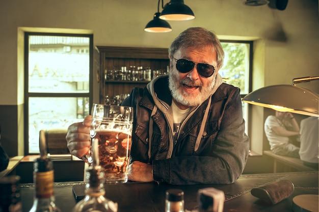 パブでアルコールを飲み、テレビでスポーツ番組を見ている年配のひげを生やした男。私の好きなティームとビールを楽しんでいます。テーブルに座っているビールのマグカップを持つ男。サッカーやスポーツのファン。人間の感情の概念