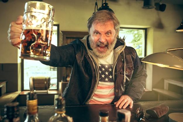 パブでアルコールを飲み、テレビでスポーツ番組を見ている年配のひげを生やした男。私の好きなティームとビールを楽しんでいます。テーブルに座っているビールのマグカップを持つ男。