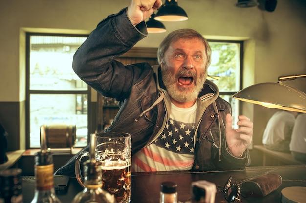 Старший бородатый мужчина пьет алкоголь в пабе и смотрит спортивную программу по телевизору. наслаждаюсь моим любимым чаем и пивом. человек с кружкой пива, сидя за столом.