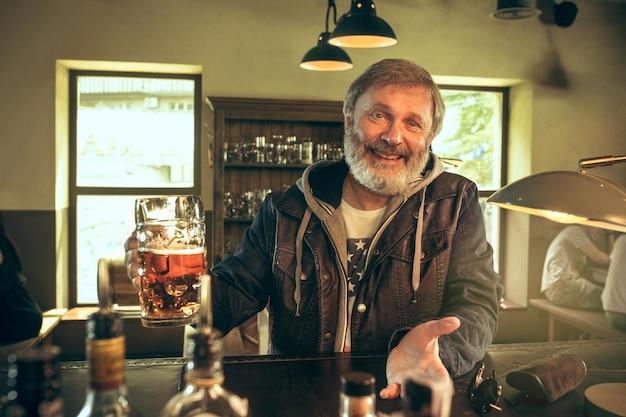 술집에서 술을 마시고 tv에서 스포츠 프로그램을 보는 수석 수염 남자. 내가 가장 좋아하는 팀과 맥주를 즐기고 있습니다. 테이블에 앉아 맥주 머그잔을 가진 남자입니다.