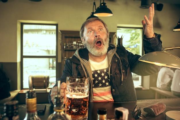 パブでアルコールを飲み、テレビでスポーツ番組を見ている年配のひげを生やした男。