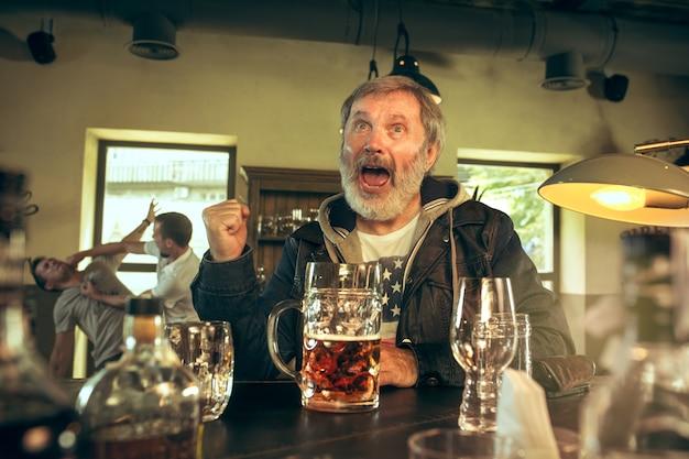 Старший бородатый мужчина пьет алкоголь в пабе и смотрит спортивную программу по телевизору.