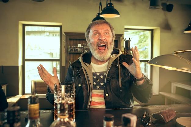 술집에서 술을 마시고 tv에서 스포츠 프로그램을 보는 수석 수염 남자.