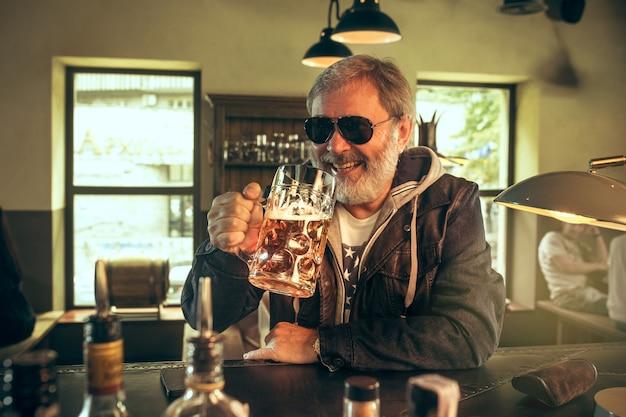 Uomo barbuto anziano che beve alcolici in un pub e guarda un programma sportivo in tv. gustando il mio brulicare e la mia birra preferiti. uomo con boccale di birra seduto a tavola. appassionato di calcio o di sport. concetto di emozioni umane