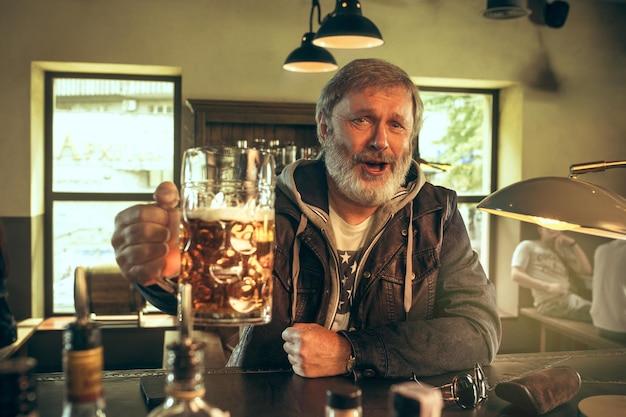 Uomo barbuto anziano che beve alcolici in un pub e guarda un programma sportivo in tv. gustando il mio brulicare e la mia birra preferiti. uomo con boccale di birra seduto a tavola.