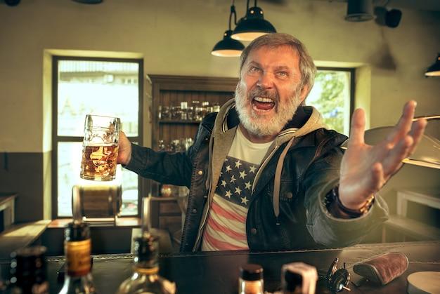 Uomo barbuto anziano che beve alcolici in un pub e guarda un programma sportivo in tv.