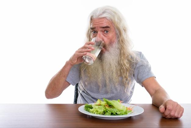 コップ一杯の水を飲む年配のひげを生やした男