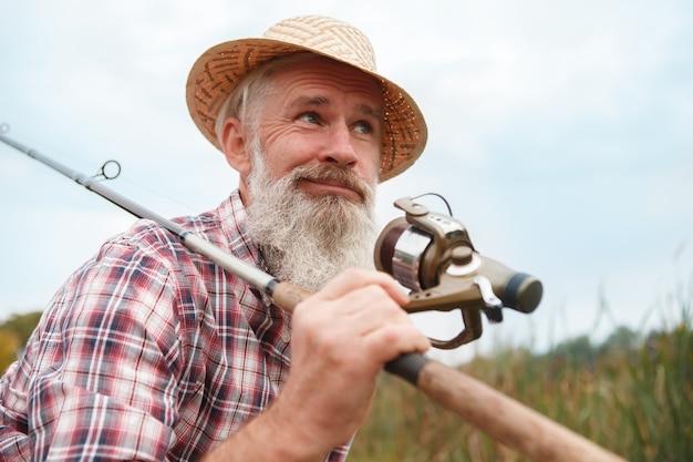 Старший бородатый мужчина, ловящий рыбу на озере