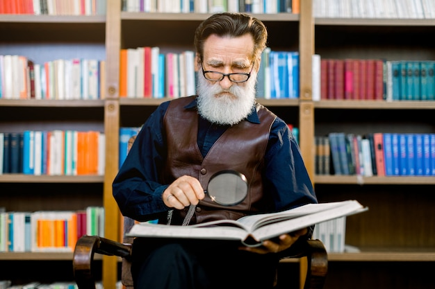 Senior bearded man in glasses, sitting and reading an old book in the library, holding magnifying glass. knowledge, learning and education concept