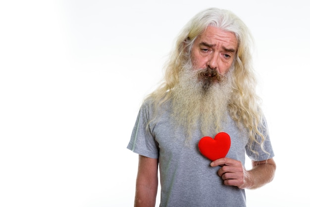 Senior bearded man holding red heart while looking down