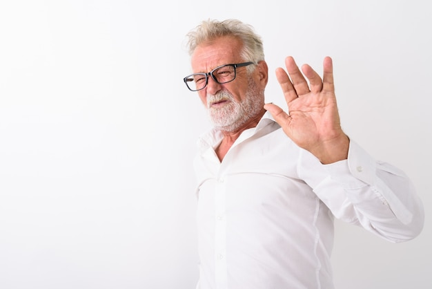 Старший бородатый мужчина с отвращением показывает знак руки стоп и в очках на белом