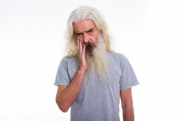 顔に手で動揺して見える年配のひげを生やした男