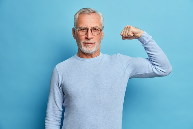Senior bearded man shows muscles after practising bodybuilding wears transparent glasses and basic jumper poses against blue studio wall