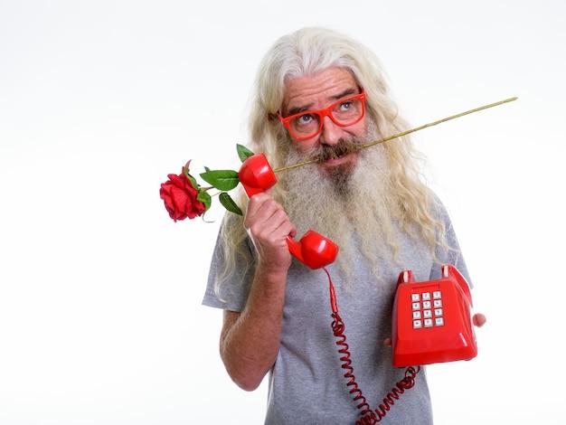 赤いバラを考えて噛む年配のひげを生やした男