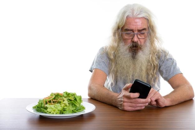 携帯電話を使用して年配のひげを生やした男