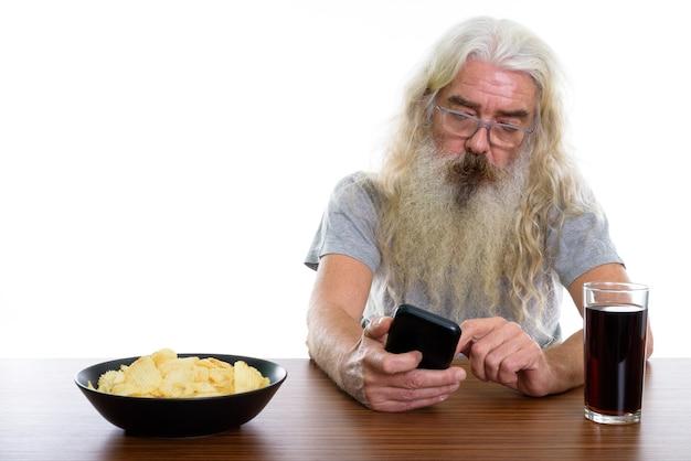 Старший бородатый мужчина с помощью мобильного телефона