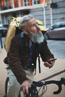 Senior bearded man working as delivery guy riding his bicycle using smart phone