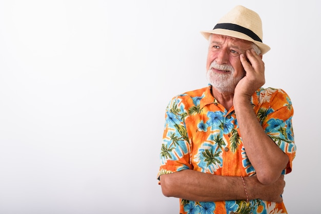 Senior bearded tourist man thinking while looking stressed and wearing hat on white