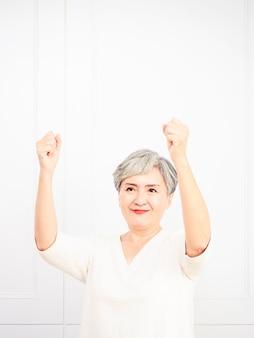 Старшая красивая азиатская женщина нося вскользь платье стоя и поднимая кулаки.